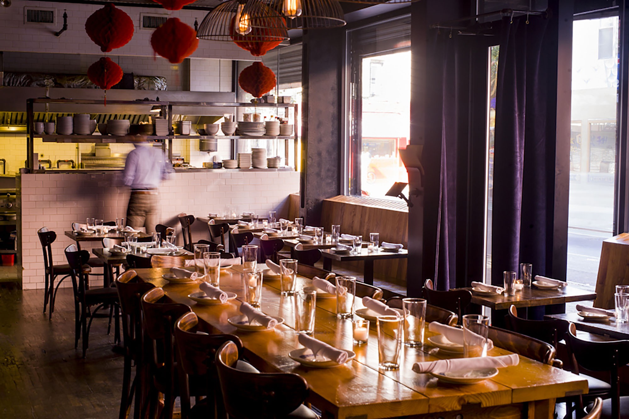A waitor is setting the tables at an upscale chinese restaurant in the Lower East Side.